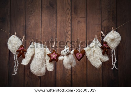 Warm baby clothes and teddy on a clothesline with Christmas decorations