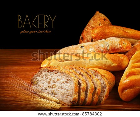 Warm baked bread, tasty crunchy buns, homemade healthy food on dinner table, with text space - stock photo