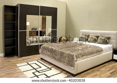 Warm bedroom with wardrobe and large bed with pillows. - stock photo