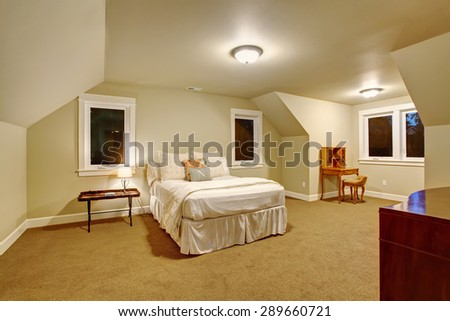 Warm bedroom with white bedding, carpet, and windows. - stock photo