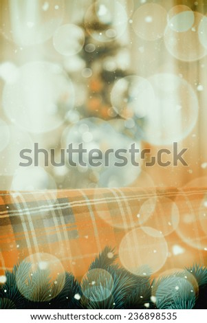 Warm blanket on the couch at christmas against twinkling red and orange lights - stock photo