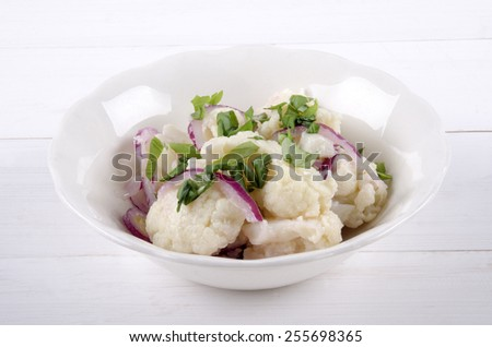 warm cauliflower salad with lilac onion and basil in a white bowl - stock photo