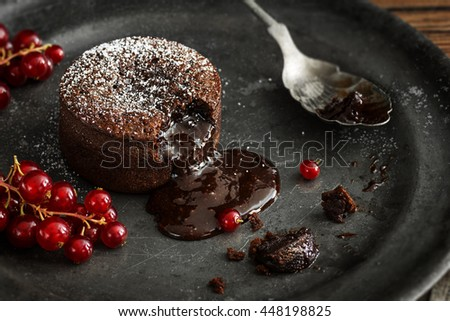 Warm Chocolate Lava Cake with Bite Taken Out of Molten Center and Red Currants on Vintage Metal Plate