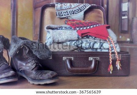 warm clothing in retro  suitcase open and placed on the floor  - stock photo