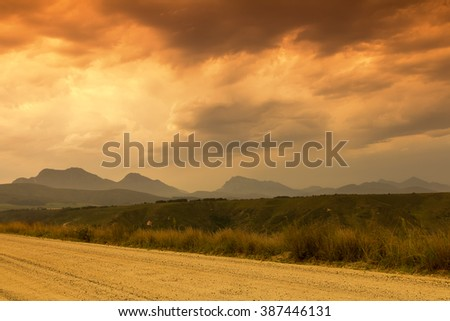 warm cloudscape with distant mountain peaks in the background and a sand road in the foreground - stock photo
