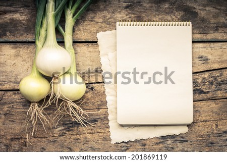 Warm color toned series of Vegetables with recipe book on wooden table. Old wood background. Menu background. Onion - stock photo