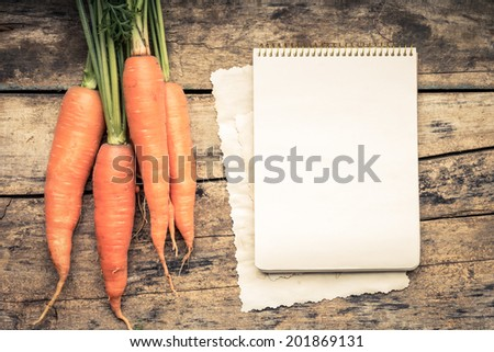 Warm color toned series of Vegetables with recipe book on wooden table. Old wood background. Menu background. Carrot - stock photo