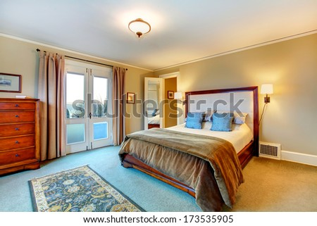 Warm colors bright bedroom. Wooden bed with queen headboard and rustic cabinet - stock photo