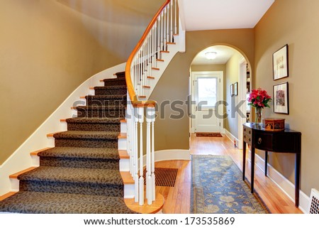 Warm colors hallway with wood stairs, rustic black cabinet and blue rug - stock photo