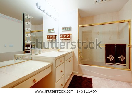 Warm cozy bathroom with glass door shower beautifully decorated with brown towels