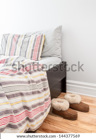 Warm cozy slippers near a bed with striped bed linen. - stock photo
