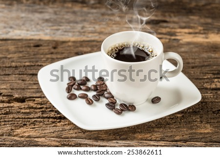 warm cup of coffee on old wooden background,Studio Shot  - stock photo
