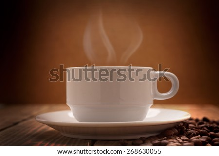 warm cup of coffee on wooden table has brown background  - stock photo