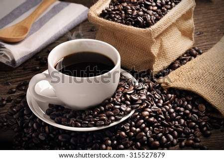 warm cup of coffee with sack inside by coffee bean on wood background