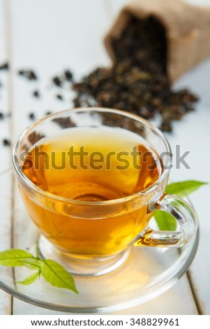 Warm cup of tea and leaves tea on white wooden
