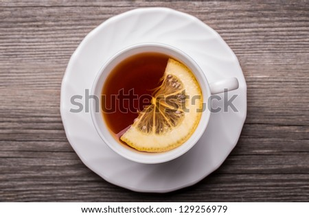 Warm cup of tea with lemon standing on wooden table. - stock photo