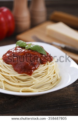 Warm, delicious spaghetti with sauce and basil on wooden table.