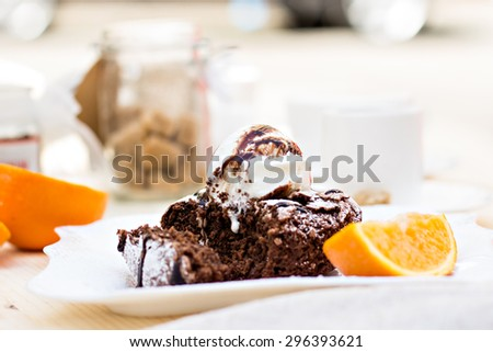 Warm dessert chocolate cake Fondant served on plate with ice-cream ball, almond chips, mint, icing, citron, cacao - stock photo