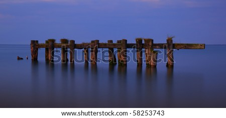 Warm evening light contrasts against a tranquil Lake Ontario as it highlights the remains of an aging pier completely separated from the shore. - stock photo