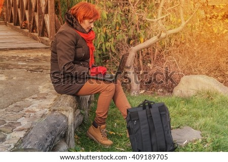 Warm fall. Spring mood of weather. Walk in the fresh air.The young woman in park with the laptop - stock photo