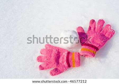 Warm female pink gloves and snowball on fresh snow. - stock photo