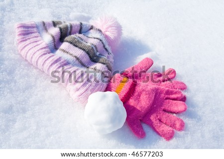 Warm female pink gloves, cap and snowball on fresh snow. - stock photo