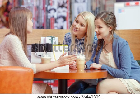 Warm friendly talk by the cocktail. Three charming young ladies having an exciting conversation sitting at the cafe in shopping mall - stock photo