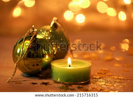 Warm glowing Christmas decoration background with a burning green candle and baubles surrounded wth scattered gold stars against a backdrop bokeh of sparkling party lights - stock photo