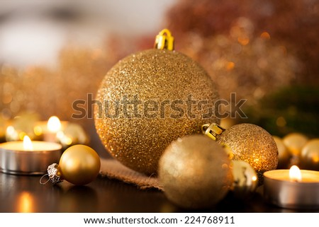 Warm gold and red Christmas candlelight background with burning tea lights amongst random gold and red baubles in a warm glowing light with copyspace - stock photo