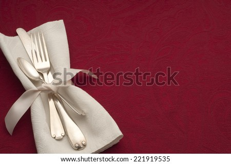 Warm Holiday or Romantic Place Setting with Sterling Silverware in White Napkin and Ribbon on Red Background with Copy space or Room for Your Text or Words.  Horizontal above view. - stock photo