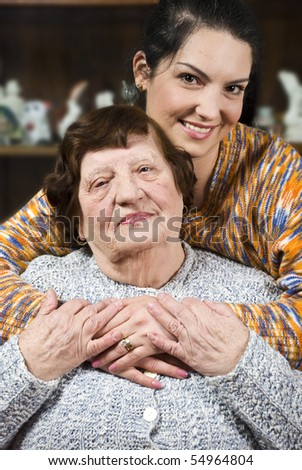 Warm hug with lots of love of a granddaughter who is visiting  her grandmother - stock photo