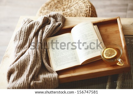 Warm knitted sweater and a book on a wooden tray