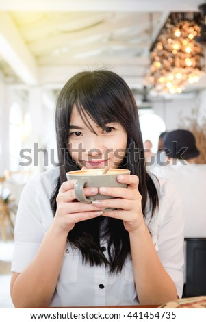 WArm light and beautiful woman with coffee cup in coffee shop white room - stock photo