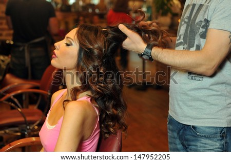 Warm light beauty shoot of brunette model in Beauty salon interior during hairstyling process - stock photo