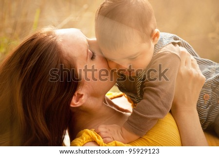 Warm Loving Mother and Son Kiss Cheek Close Up - stock photo