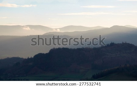 Warm morning sunlight over the valley surrounding Braithwaite, Derwent Fells, from the trail leading from Grisedale Pike in the Lake District, Cumbria, England. UK.