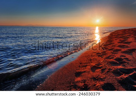 Warm ocean beach sunrise with breaking wave and footprints in sand - stock photo
