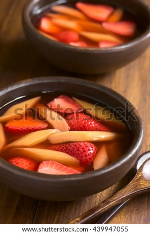 Warm or cold fruit soup made of strawberry and rhubarb served in rustic bowls, photographed on dark wood with natural light (Selective Focus, Focus one third into the image) - stock photo