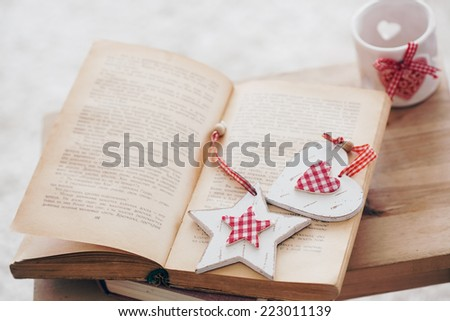 Warm photo of cozy moments: vintage book with Christmas decor and candlestick on wooden bench, shallow focus. - stock photo