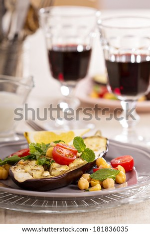 Warm salad with baked eggplant, chickpeas, tomatoes and herbs