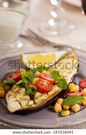 Warm salad with baked eggplant, chickpeas, tomatoes and herbs - stock photo