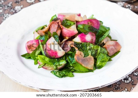 Warm salad with fried radishes, spinach, bacon, cream cheese feta