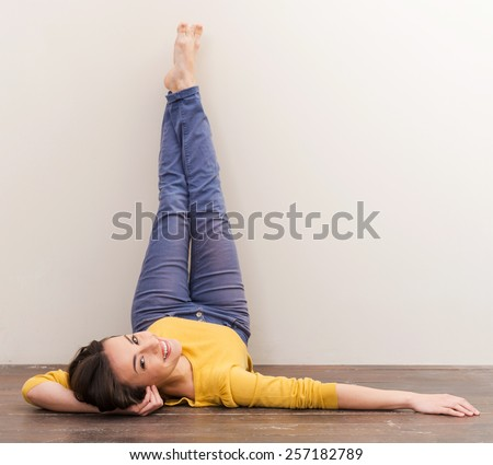 Warm smile. Beautiful young woman looking at camera and smiling while lying on the floor and leaning her legs at the wall - stock photo