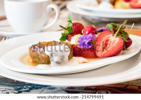 Warm, spicy baked apple with honey caramel sauce and bulgarian yoghurt, and fresh fruit decorated with edible purple flowers. Regional cuisine with a modern twist. Served in bed and breakfast inn. - stock photo