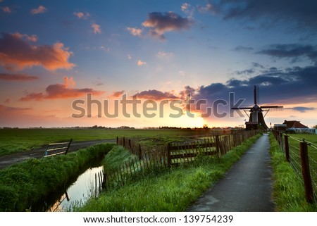 warm spring sunrise behind windmill, Netherlands - stock photo