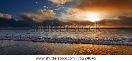 Warm sun and cold water meeting on the beach. - stock photo