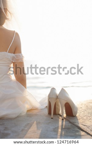 warm tone photograph of a bride sitting on concrete ground next to the beach with her shoes on the right side. Left side of the photo left available for your text