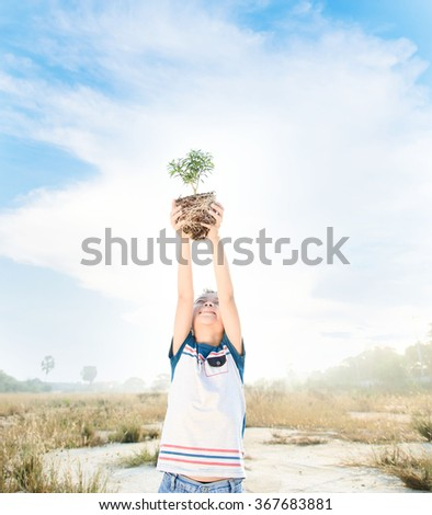 Warm tone, young asian boy lift little plant to the sky. Earth day concept - stock photo
