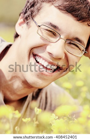 Warm toned close up portrait of young hispanic man wearing glasses, smiling perfect healthy toothy smile in spring park outdoors - humor, dentistry or ophthalmology concept - stock photo