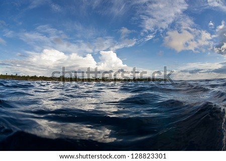 Warm, tropical waters surround a distant Philippine island while white clouds cruise through the blue sky. - stock photo